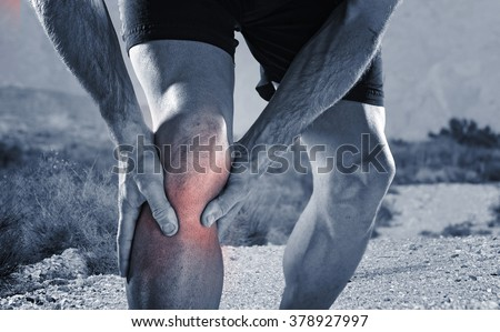 young sport man with strong athletic legs holding knee with his hands in pain after suffering muscle injury during a running workout training in trail desert dirt road in black and white - stock photo