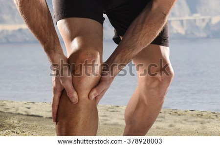 young sport man with strong athletic legs holding knee with his hands in pain after suffering muscle injury during a running workout beach training in muscular or ligament wound  - stock photo