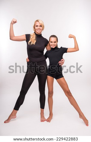 Young sport  mother and her   daughter teenager showing their  muscles looking at camera  isolated on white background  - stock photo