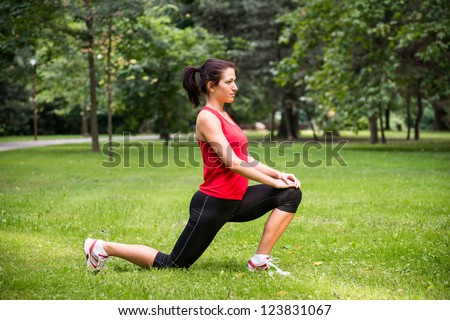Young sport woman exercising before jogging - outside in nature - stock photo