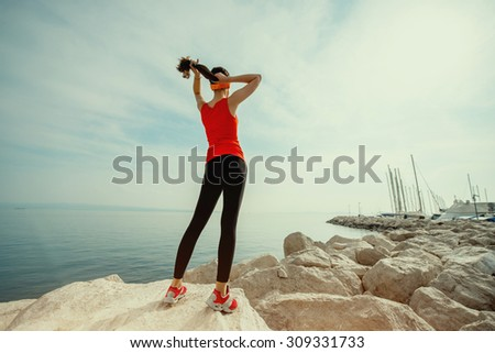 Young sport woman in red shirt and sneakers standing on the rocky beach and looking at the sun in the morning. General plan. Photo with cross processing filter - stock photo