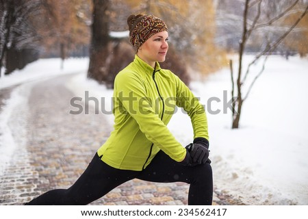 Young sport woman model doing exercises during winter training outside in cold snow weather in park - stock photo