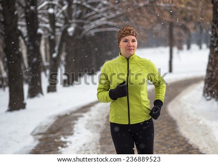 Young sport woman model  jogging during winter training outside in cold snow weather in park  - stock photo