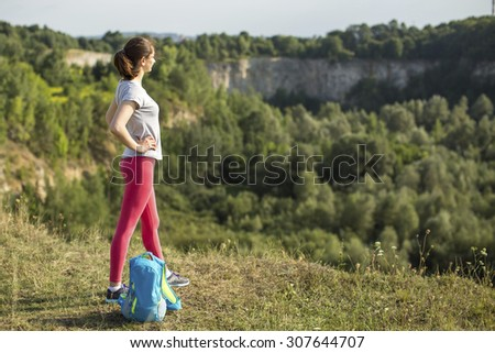 Young sport woman traveler on the top of mountain. - stock photo