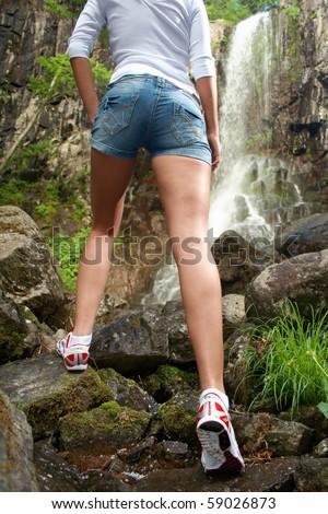 Young sporting girl walking outdoor near to waterfall - stock photo