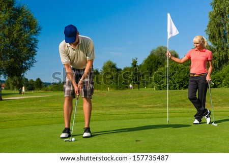 Young sportive couple playing golf on a golf course, he is putting at the green - stock photo