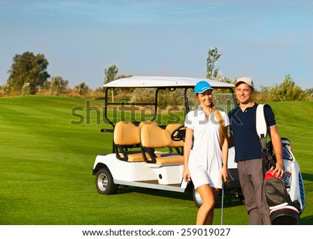 Young sportive couple playing golf on a golf course. Standing near the golfcar - stock photo