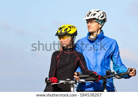 Young sportive couple with mountain bikes looking in one side  - stock photo