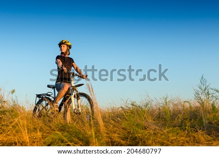 young sportive female biker at sunset light  - stock photo