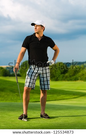 Young sportive man playing golf on a course, he might play a golf tournament - stock photo