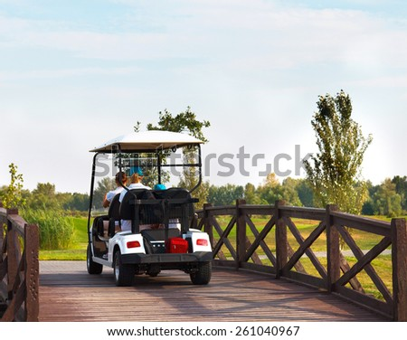 Young sportive people in the golfcar on the golfcourse - stock photo