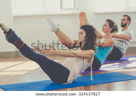 Young sportive trio group boy and two girls are practicing yoga exercises in the studio - stock photo