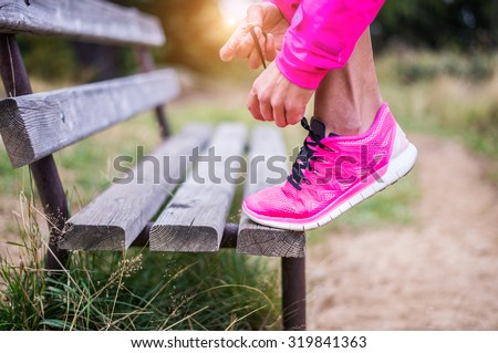 Young sportive woman getting ready to start running workout - Athlete running outdoors at sunset - Attractive girl making sport to lose weight and stay fit - stock photo