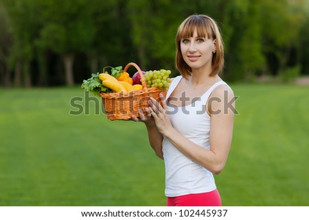 Young sportive woman with basket of fruits - stock photo