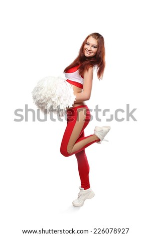 Young sports flexible cheerleader girl in red sweatpants and red top holding pom-poms. Young high school female dancer standing with pom-poms on isolated white background. - stock photo