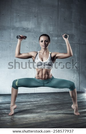 Young sports sexy fitness woman with dumbbells stretching. - stock photo