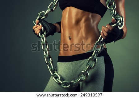 Young sports sexy woman body with heavy chain. - stock photo