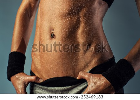 Young sports woman abdominal muscles. Sexy wet body on gray background. - stock photo