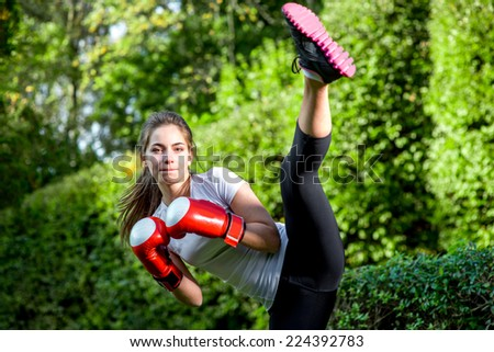 Young sports woman boxing in the park - stock photo