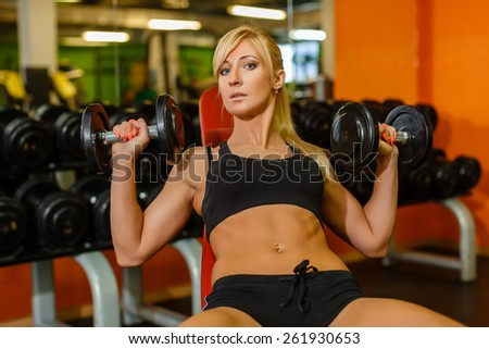 Young sports woman doing exercises with dumbbells in the gym. Fitness. - stock photo