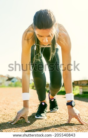Young sports woman in start position preparing to run. - stock photo
