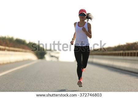 young sports woman runner running on city road - stock photo