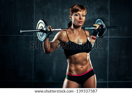 Young sports woman with barbell. - stock photo