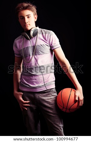 Young sportsman basketball player posing with ball. Over black background. - stock photo