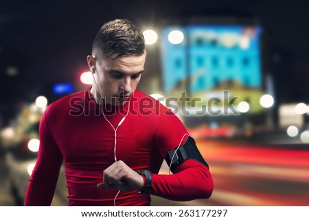Young sportsman jogging in the night city - stock photo