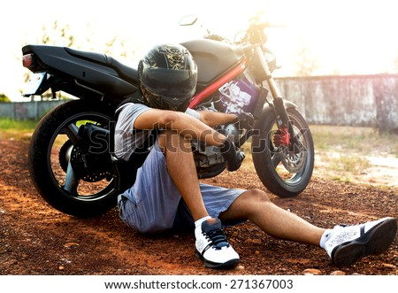 Young sportsman posing on helmet opposite the sunset.Motorcycle extreme sport.sportsman on motorcycle wear helmet,motocross clothes ,cool motorcycles man in sunglasses and helmet - stock photo