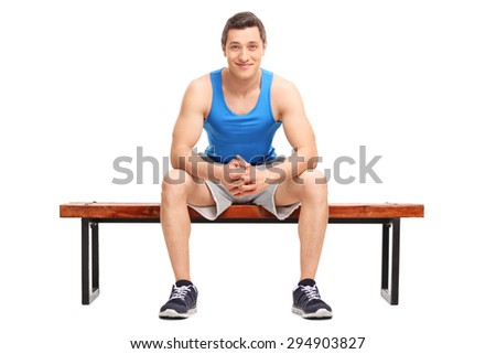 Young sportsman sitting on a wooden bench and looking at the camera isolated on white background - stock photo