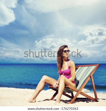 Young, sporty, beautiful and happy woman relaxing on a summer beach - stock photo
