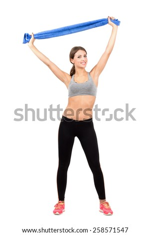 Young sporty beauty holding towel over her head. Full body length portrait isolated over white background. - stock photo