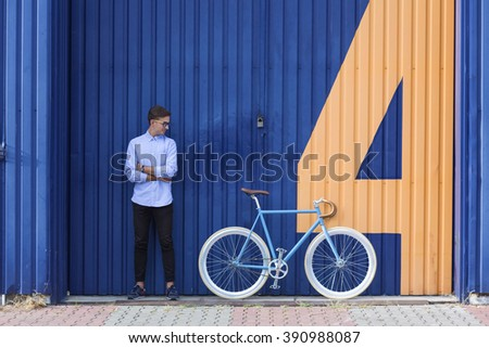 Young sporty businessman standing beside his cycle - stock photo