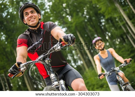 Young sporty couple riding on bicycles at the forest road. Man in front of woman. - stock photo