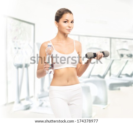 Young, sporty, fit and beautiful girl with the dumbbells and the bottle of water training in the gym - stock photo