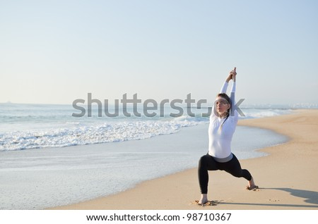 Young sporty girl doing exercise on the beach - stock photo