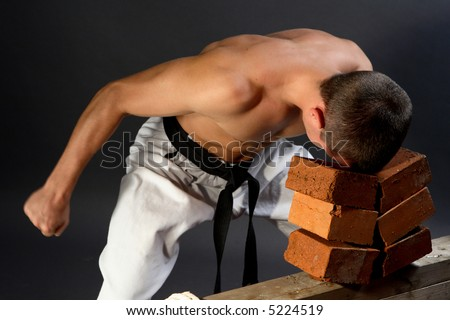 Young sporty karate man breaking three bricks on gray background - stock photo