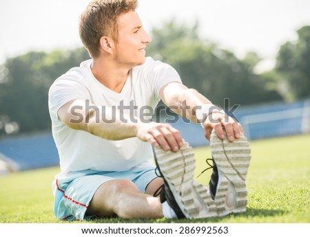 Young sporty man prepares to run sprint. Training outdoors at sunrise. - stock photo