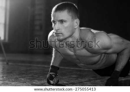 Young sporty man pushed off the floor. Black and white photo. - stock photo
