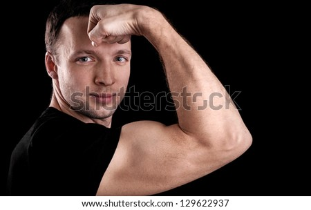 Young sporty man shows biceps, portrait isolated on black background - stock photo