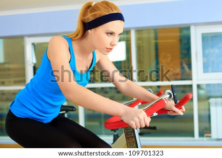 Young sporty woman doing exercise on bicycle in the gym centre. - stock photo