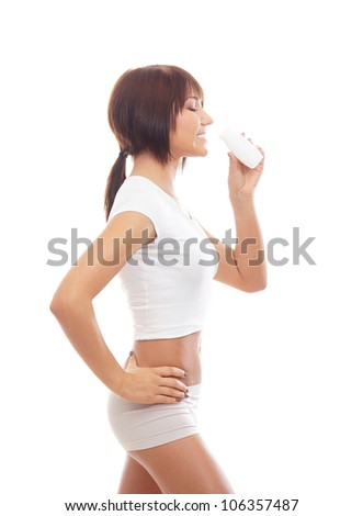 Young sporty woman drinking from the bottle isolated on white - stock photo