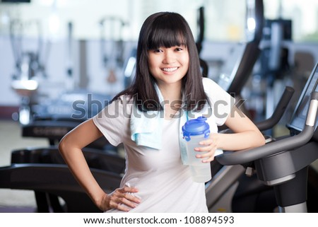 Young sporty woman holding bottle of water and looking at camera in fitness club - stock photo