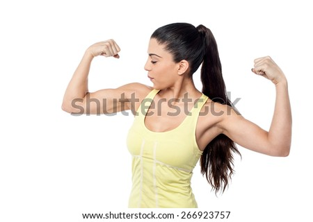Young sporty woman looking at her biceps - stock photo
