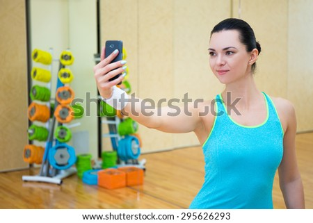 young sporty woman making selfie photo on smartphone in gym - stock photo