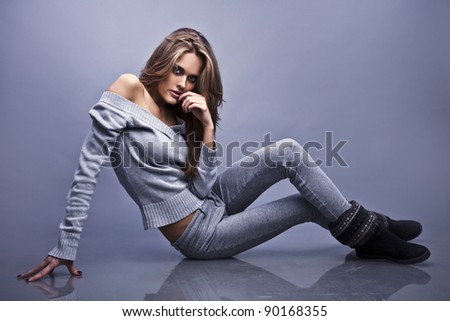 Young sporty woman siting on the studio floor - stock photo