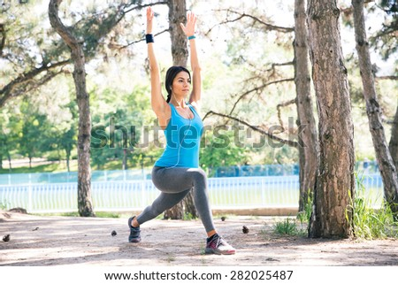 Young sporty woman stretching outdoors in park - stock photo