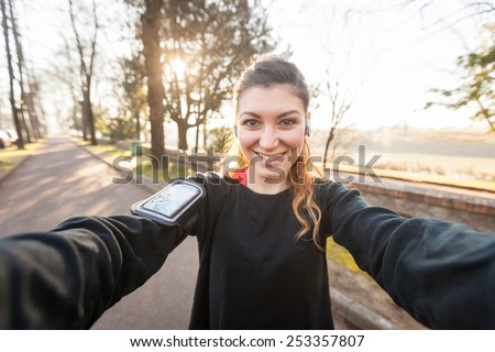 Young Sporty Woman Taking a Selfie at Park. She is Looking at Camera, that is the POV, Point of View, of the photo. She has a Smart Phone Holder on her Arm and Listen Music with Earphones. - stock photo