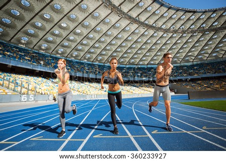 Young sporty women and man running on racetrack. Fit well formed people are at large nice modern stadium - stock photo
